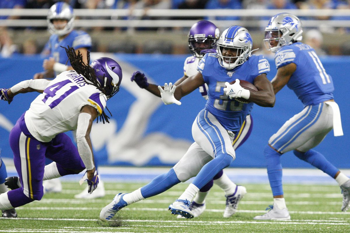 Detroit Lions running back Kerryon Johnson runs the ball against Minnesota Vikings defensive back Anthony Harris during the first quarter at Ford Field.