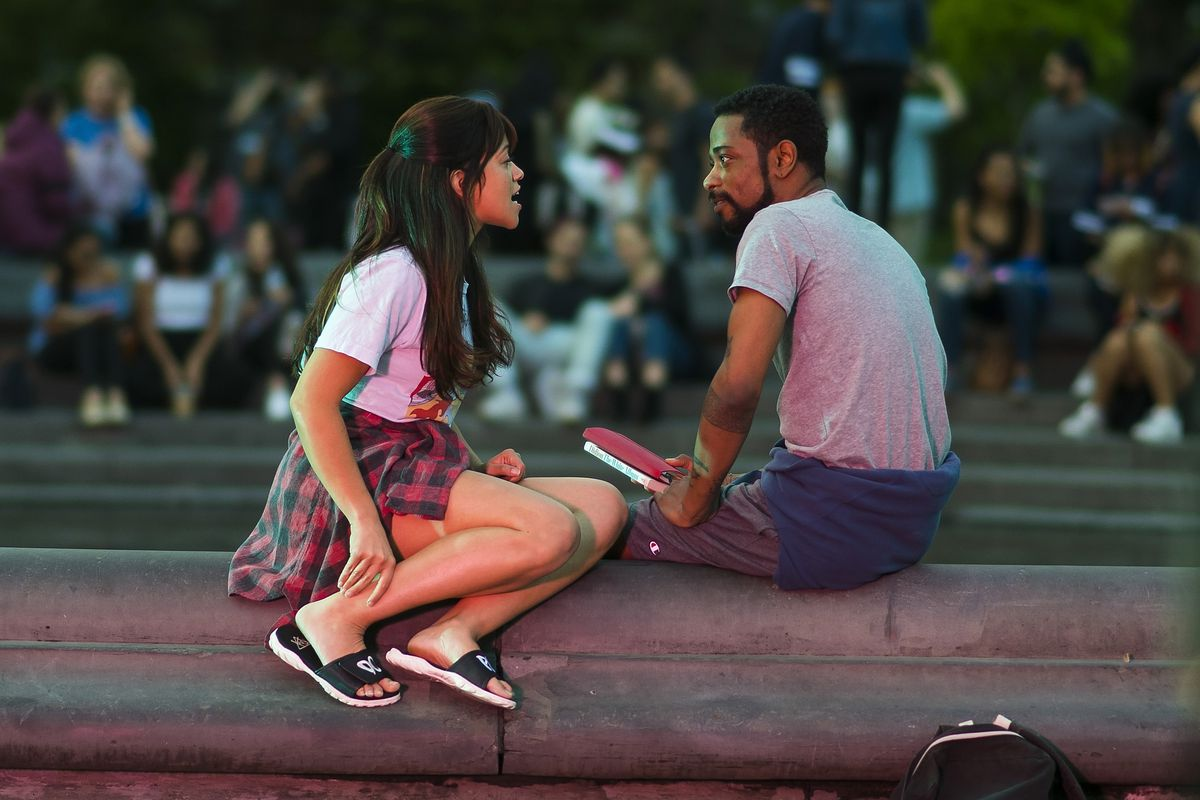 Two people sit facing each other on a park railing.
