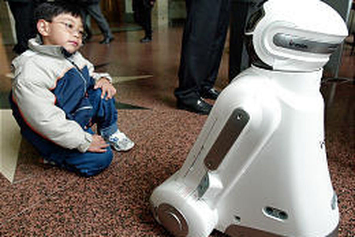 A child watches the Korean IROBI, an Internet-based family robot featuring education, home security, daily life management, entertainment, message delivery at the World Robotics Survey in Geneva, Switzerland.