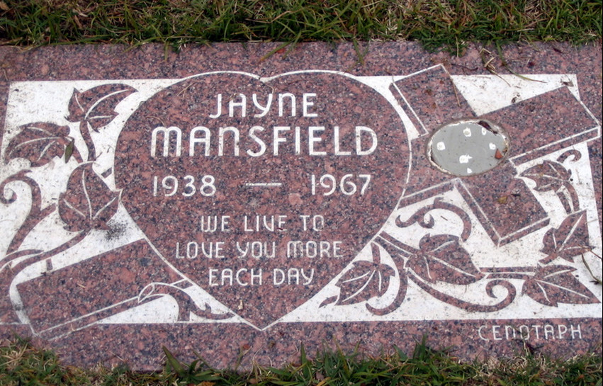 A brown and white gravestone in the Hollywood Forever cemetery. The words on the gravestone read Jayne Mansfield 1938-1967 We live to love you more each day.