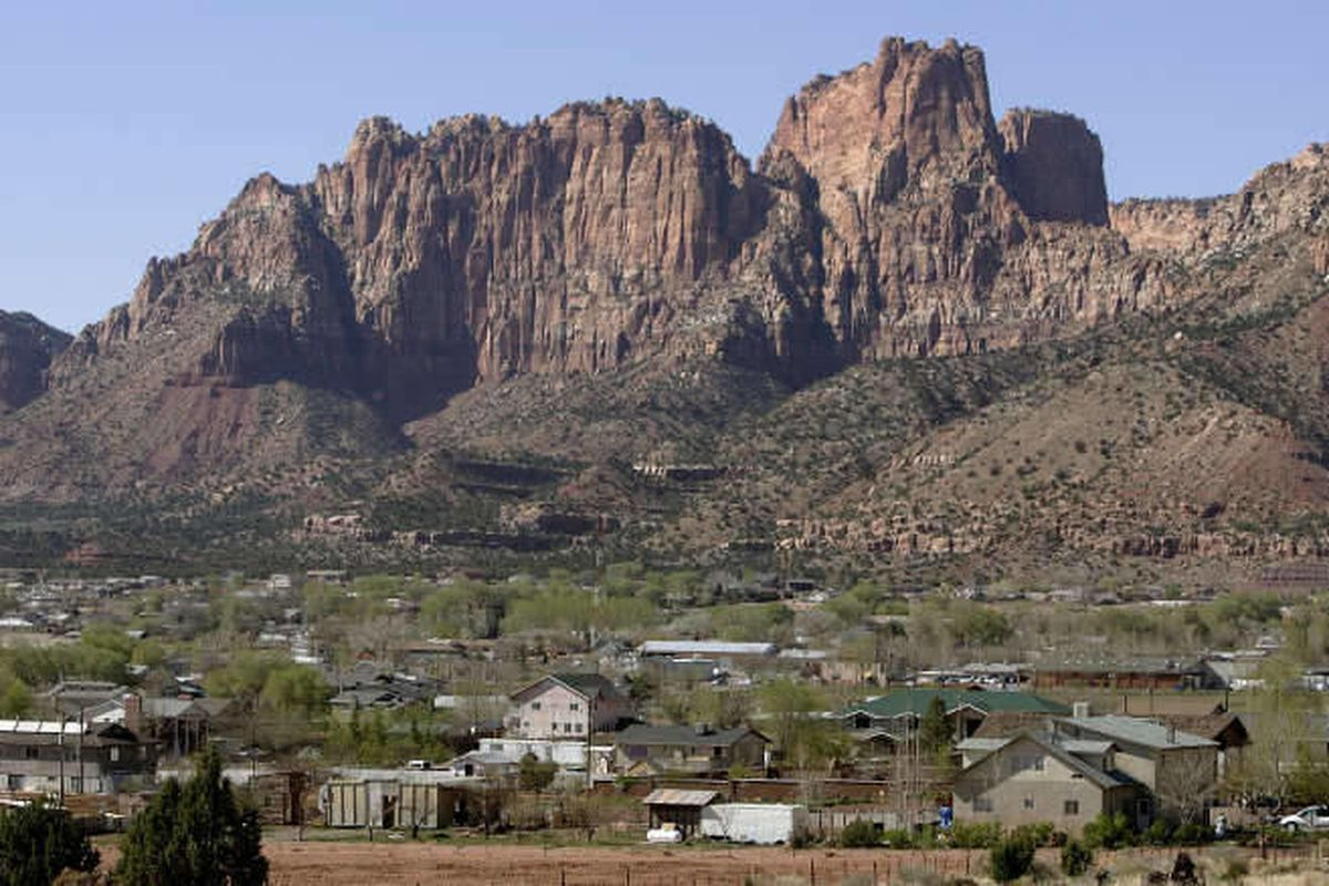 Hildale, Utah sits at the base of red rock cliff mountains with its sister city, Colorado City, Ariz. in the foreground Thursday, April 20, 2006.