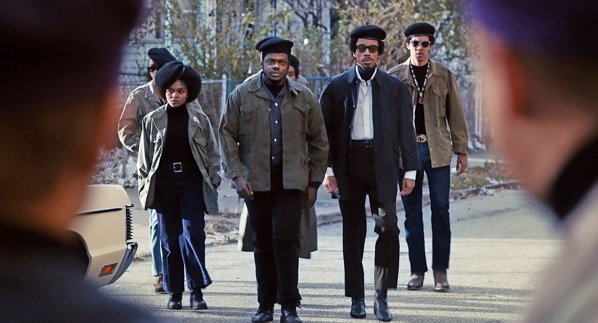 A group of young Black people in berets walk in a group.