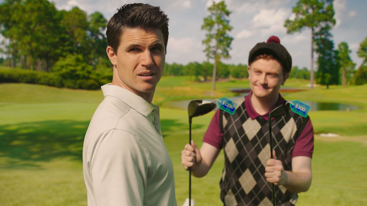 A young man is offered two golf clubs with digital price tags by a caddy.