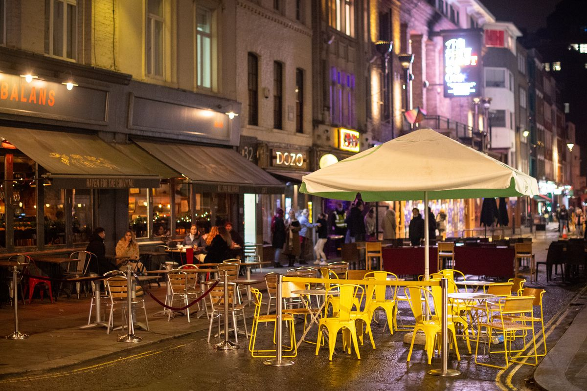 A restaurant in Soho with empty outdoor seating on the pavement and in the street