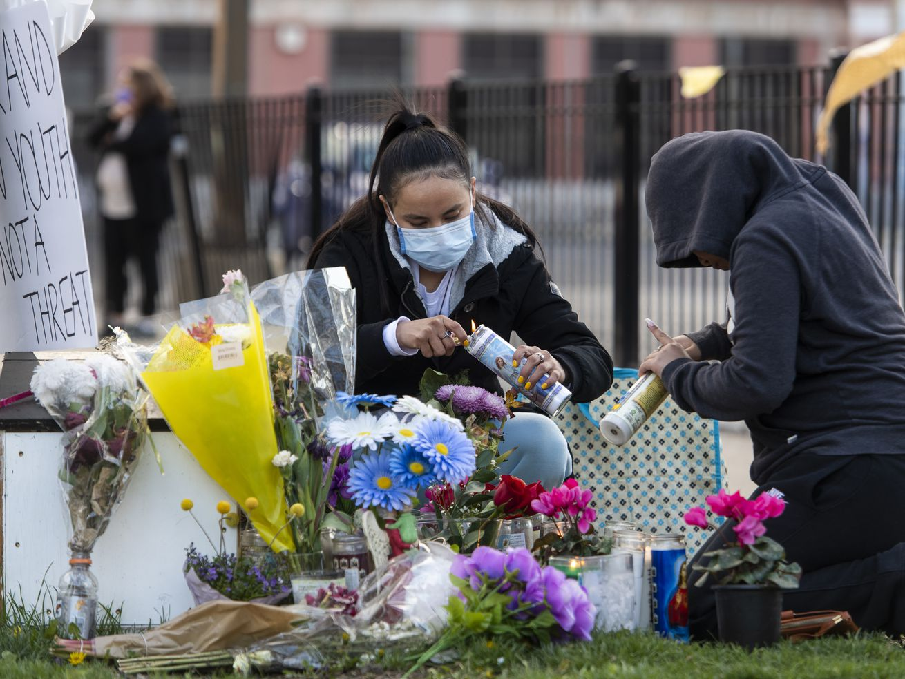 Two women from Little Village tend to the memorial for Adam Toledo near 24th St. and Sawyer Avenue. Toledo, a 13-year-old, was shot and killed by a Chicago police officer.
