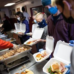 Chad Seeley, second from right, and other volunteers prepare hot meals to be distributed at the Rescue Mission of Salt Lake in Salt Lake City on Saturday, Dec. 19, 2020. Volunteers handed out hot meals as well as hundreds of pairs of boots to people experiencing homelessness.