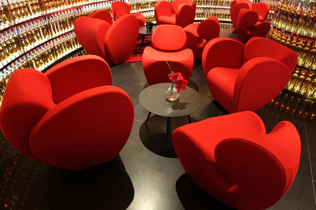 Red plush seating next to a backlit angular wall of whiskey
