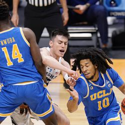 BYU guard Alex Barcello (13) gets screened out by UCLA forward Kenneth Nwuba (14) as he tries to defend UCLA guard Tyger Campbell (10) during the first half of a first-round game in the NCAA college basketball tournament at Hinkle Fieldhouse in Indianapolis, Saturday, March 20, 2021.