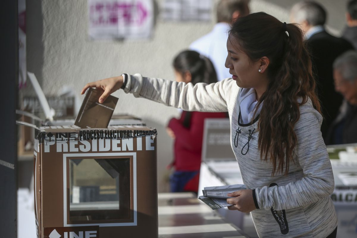 A woman casts her vote for president during general elections in Mexico City, Sunday, July 1, 2018. Sunday's elections for posts at every level of government are Mexico's largest ever and have become a referendum on corruption, graft and other tricks used