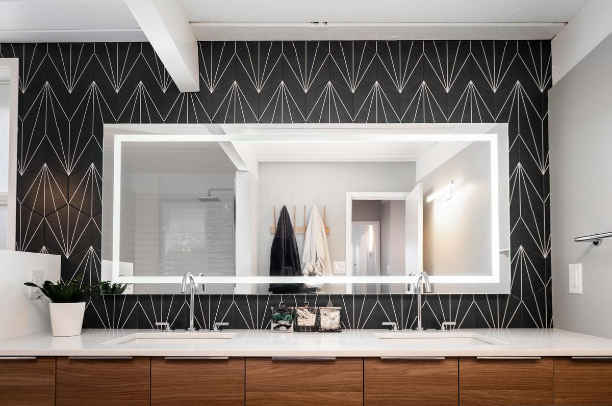 A double sink bathroom has wood cabinets, a mirror, and a bold black and white geometric print on the walls.
