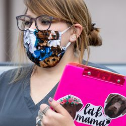 Savanah Hendershott, a vet technician wears a mask her father-in-law made her while talking with a pet owner at Sugar House Veterinary Hospital in Salt Lake City on Thursday, May 21, 2020. The facility's lobby remains closed amid the COVID-19 pandemic, and pet owners are asked to call the hospital and wait in the parking lot for a technician to walk their pets inside and return them after their appointment.