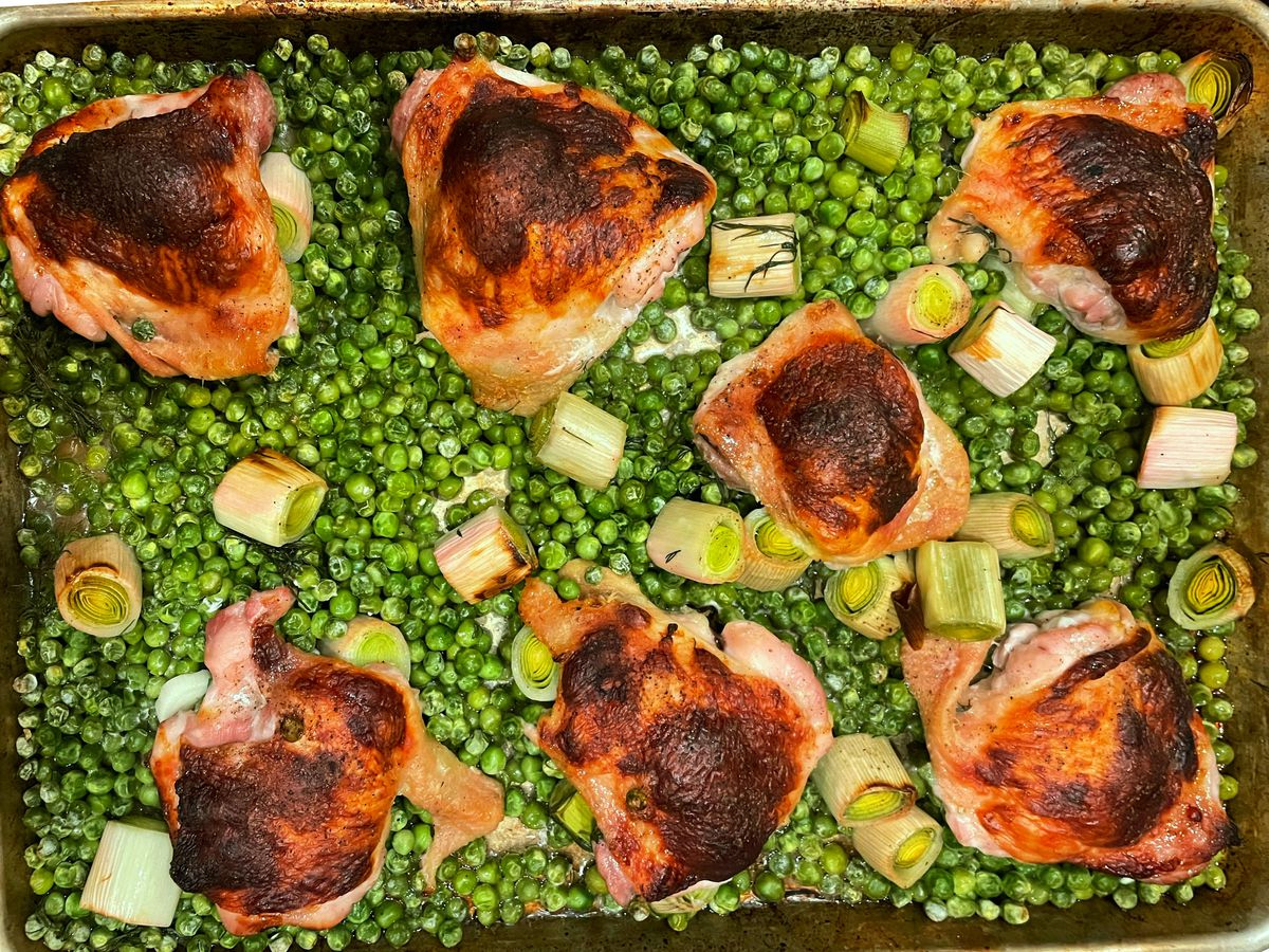 a sheetpan covered in peas and chicken thighs.