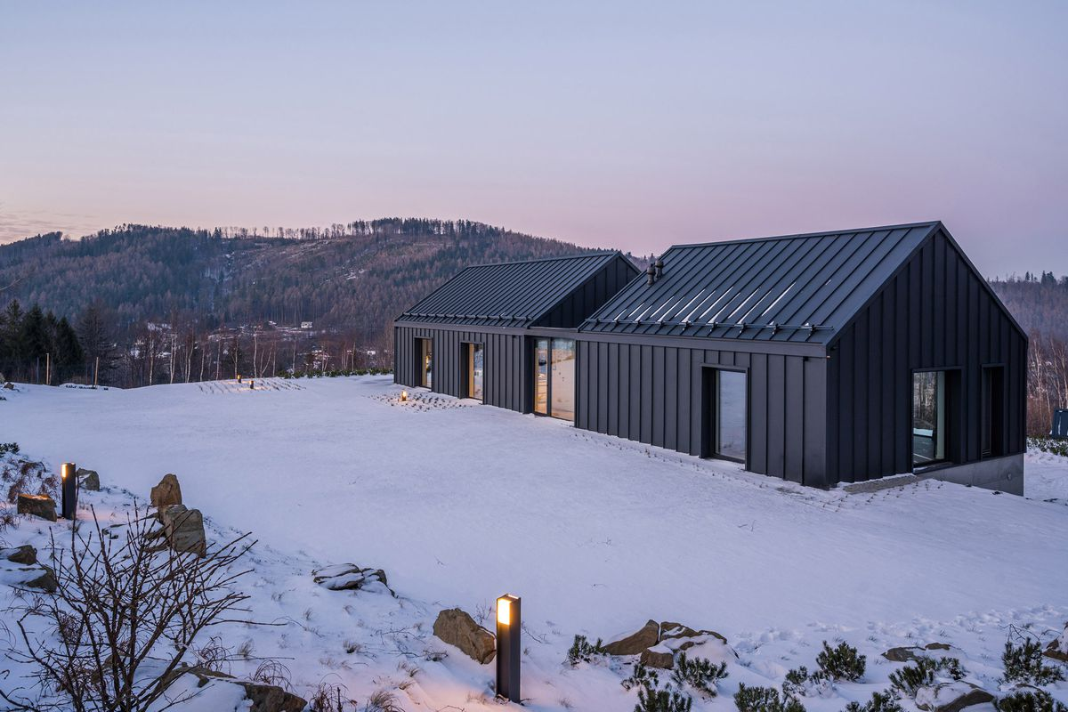 Black house near snow-covered mountains.