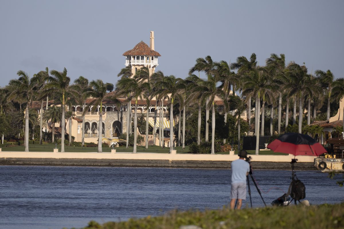 Mar-a-Lago in Palm Beach, Florida, as seen from across the Intracoastal Waterway. A man stands in the foreground with a camera on a tripod.