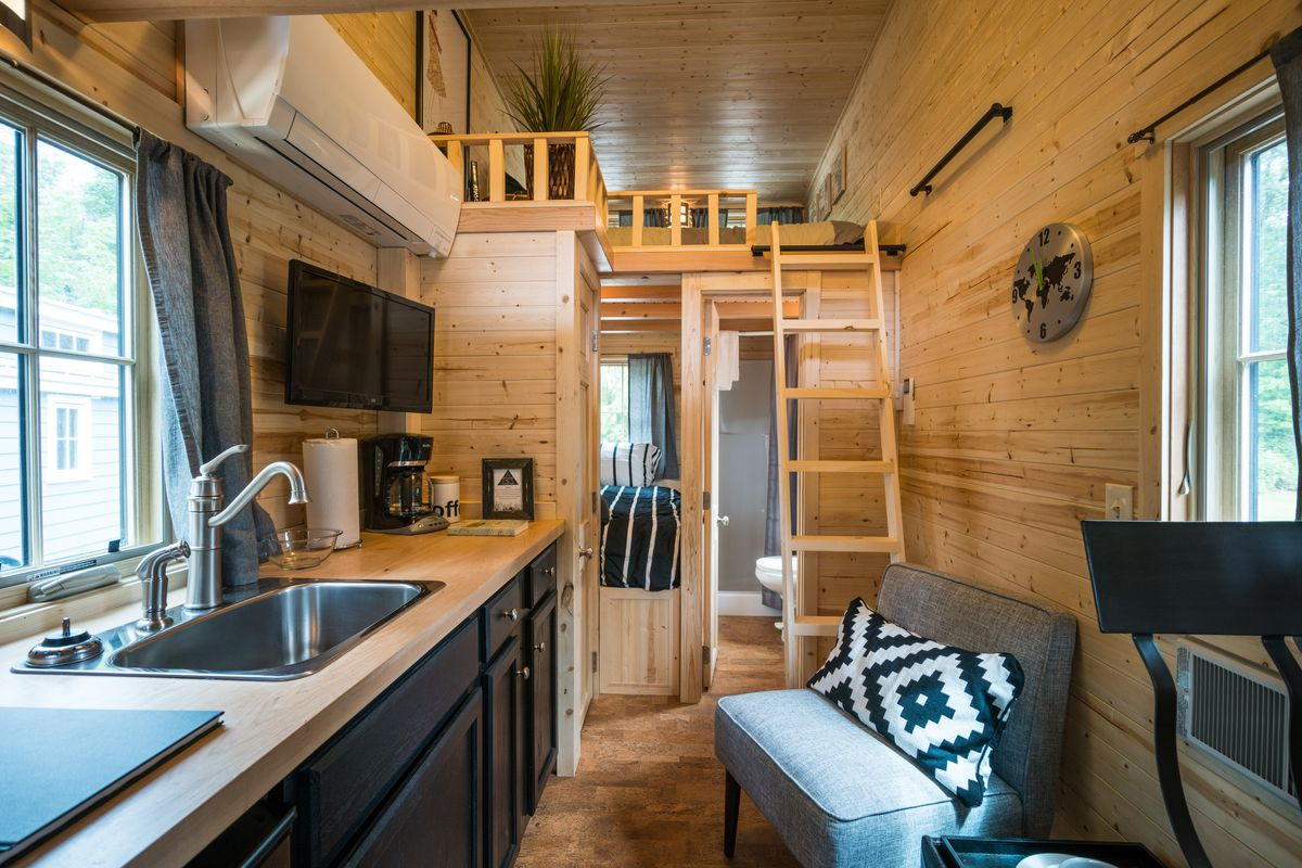 The inside of a tiny home, with a small kitchen, lofted bed, and chair.