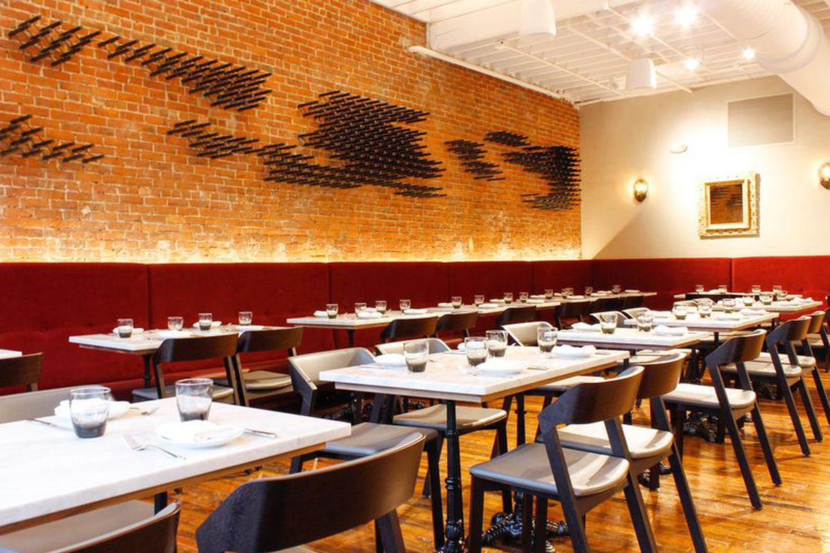 A restaurant interior with a brick wall and red booths