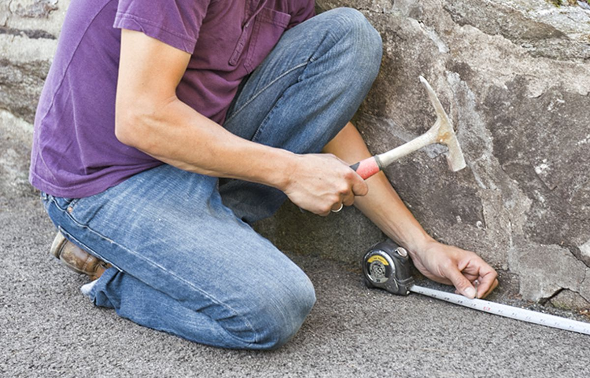 Man Measuring Driveway For Building Driveway Apron