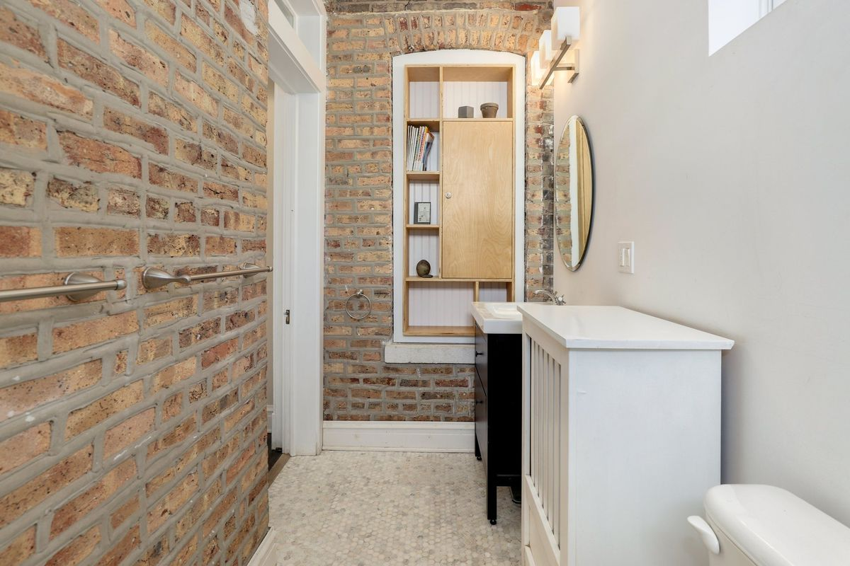The guest bathroom with a built in shelf and exposed brick.