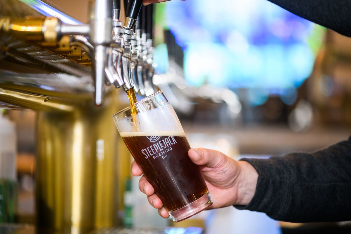 A white hand holds a pint glass filled with a dark, coffee-brown beer, as he pours it from the brewery's taps.