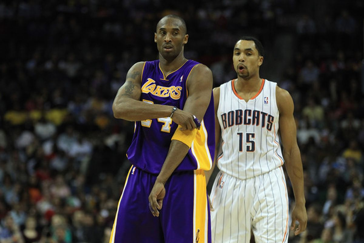 CHARLOTTE NC - FEBRUARY 14:  Kobe Bryant #24 of the Los Angeles Lakers stands in front of Gerald Henderson #15