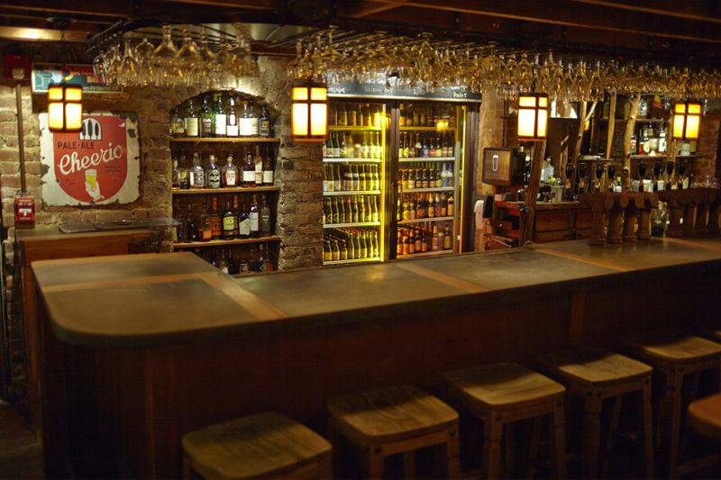 The interior of a pub. There is a bar with stools. There are shelves full of liquor behind the bar.