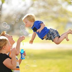 """Nikolas, Ali and William Lawrence blow bubbles. Alan Lawrence photographed his son William in a series titled """"Wil Can Fly"""" on his blog, <a href=""""http://thatdadblog.com/"""">thatdadblog.com</a>"""