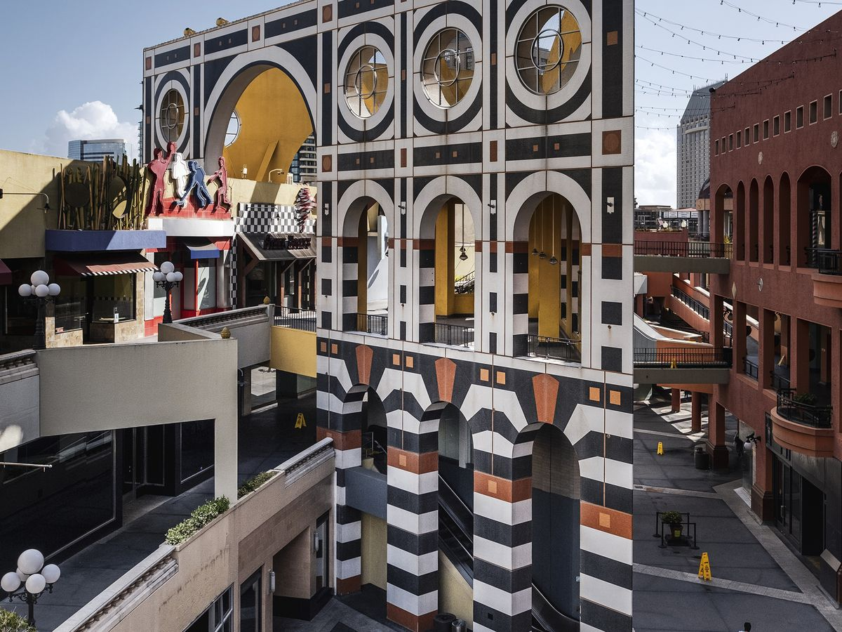 Postmodern-styled outdoor mall plaza with black and white striped detail and a raised platform