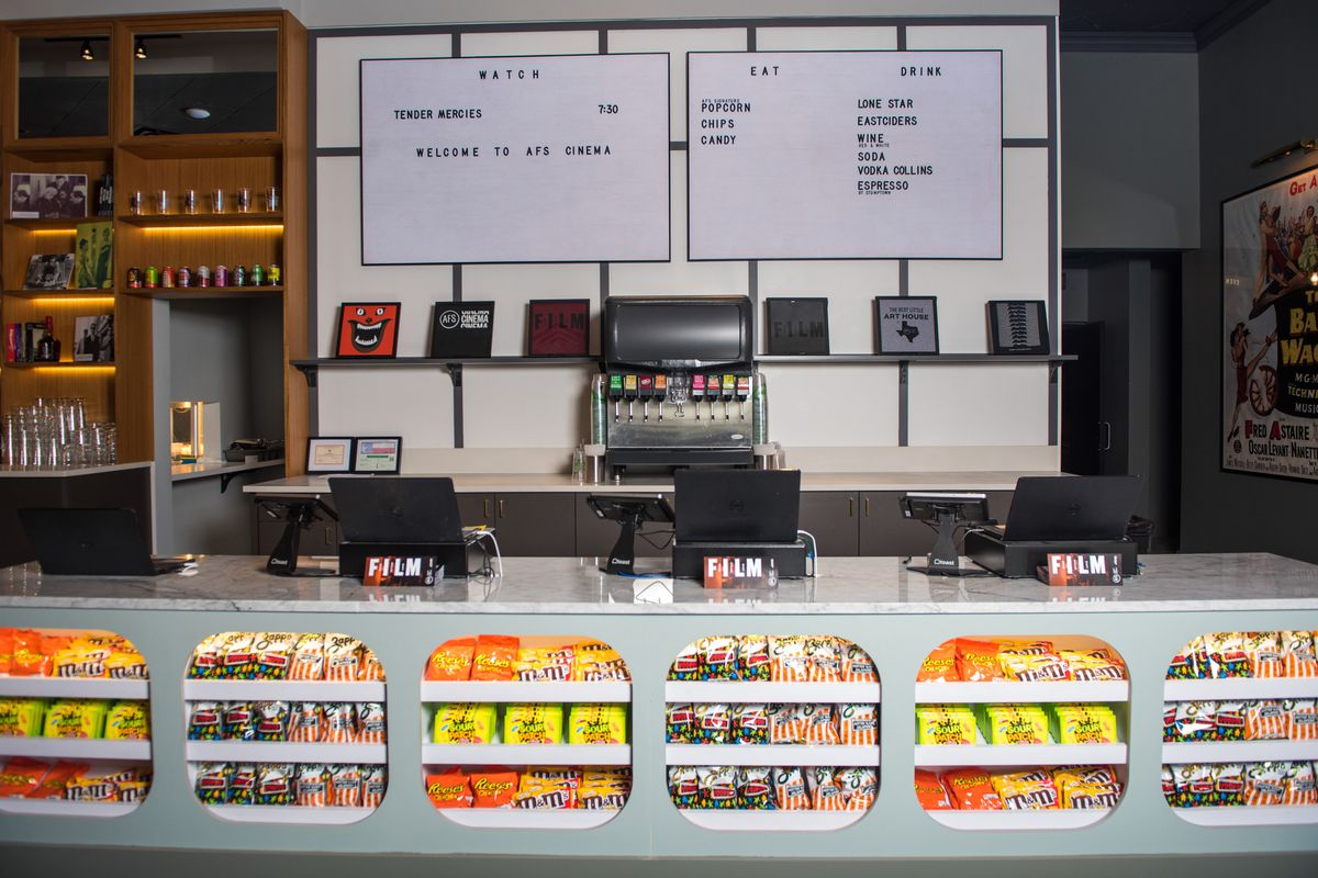 A cool-looking snack bar with a marquee that has film schedule on it and film collectibles displayed underneath