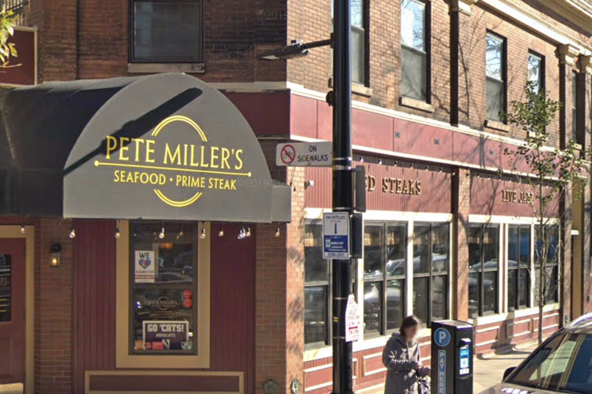 """A brick building with a black awning that reads """"Pete Miller's Seafood, Prime Steak"""" on a sun-drenched street."""