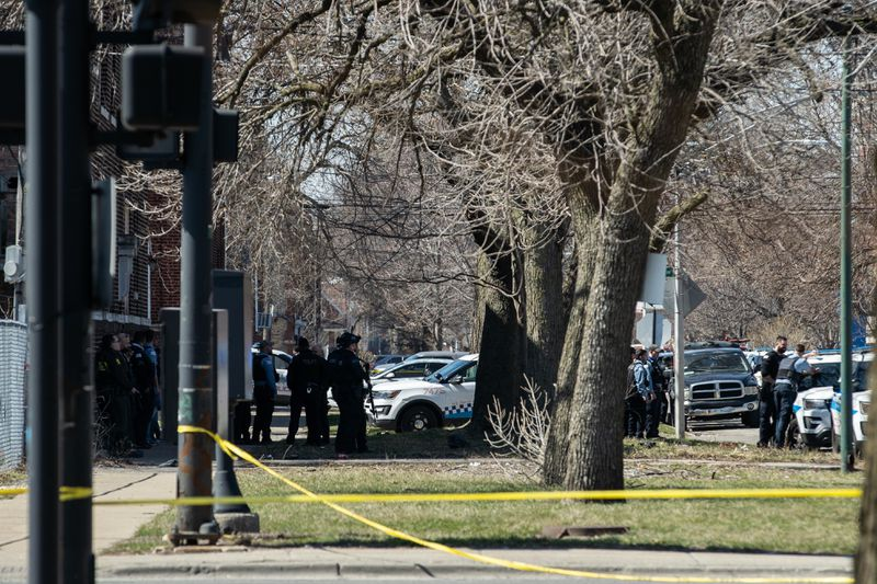 Police officers stand near an active shooter scene near 207 N. La Crosse Ave. on Saturday.