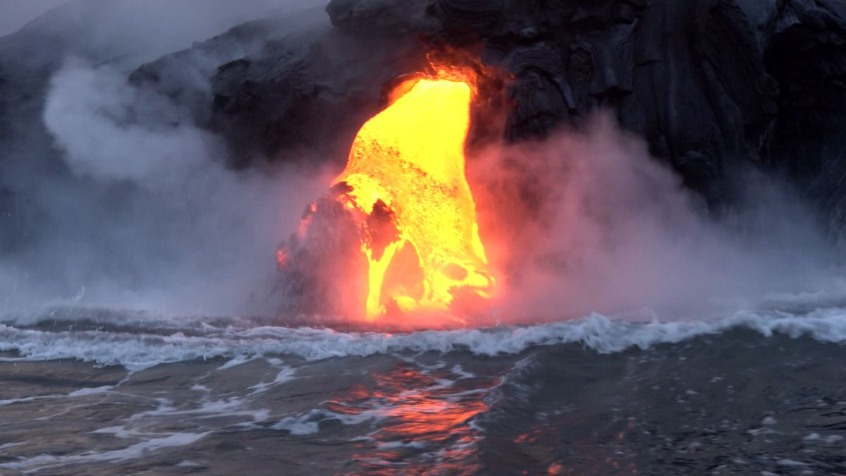 Lava from Kilauea volcano flowing into the ocean, creating new land.