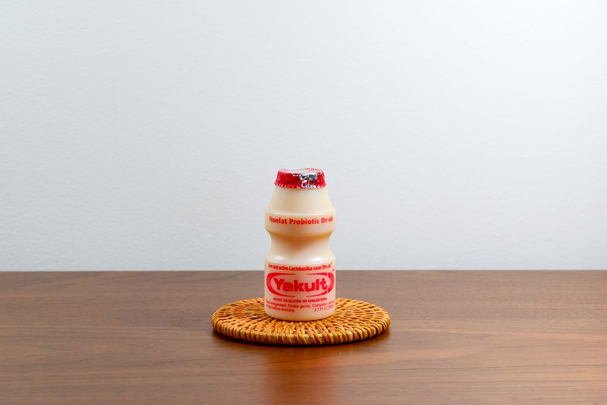 A container of Yakult on a coaster on a tabletop.