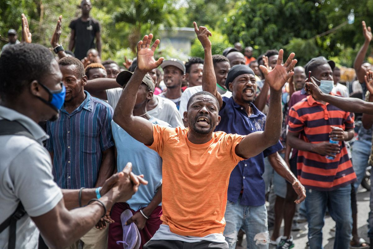 The crowd reacts near the Petionville Police station where armed men, accused of being involved in the assassination of President Jovenel Moise, are being detained in Port au Prince on July 8, 2021.