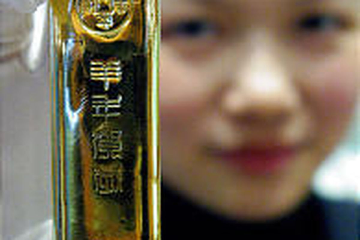 A Chinese saleswoman holds up a 200 gram gold bar that was on display at a department store in Nanjing, eastern China, in 2002.