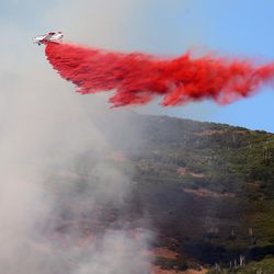 A SEAT tanker drops retardant on a fire burning on the mountain above Farmington on Friday, June 23, 2017.