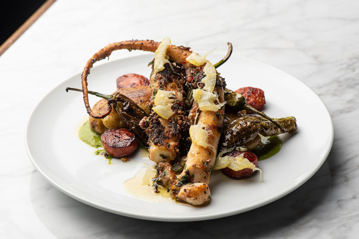 A curl of octopus, grilled, on a white plate.