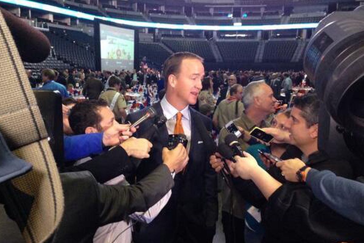 Broncos quarterback Peyton Manning greets the media at a Boy Scouts of America breakfast Wednesday.