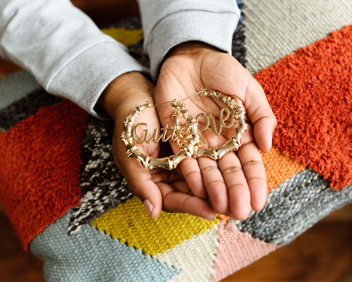 "Two hands hold gold hoop earrings that read ""Cutie Pie."""