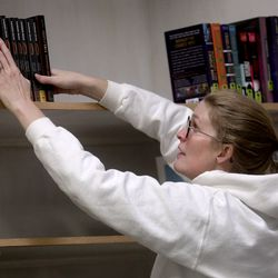 Olivia Wilkinson, Utah State Library cataloguer, organizes new books at the Odyssey House Adolescent Residential Center in Salt Lake City on Wednesday, Oct. 30, 2019.Staff from the state library division are using a federal grant to redo the library at the center to add age-specific books for the teens in treatment.
