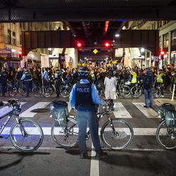 Chicago police officers keep watch as at least 1,000 protesters march through the Loop to demand every vote be counted in the general election, Wednesday night, Nov. 4, 2020.