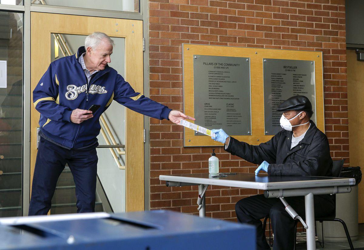 Milwaukee Mayor Tom Barrett gets help with his ballot on Saturday.
