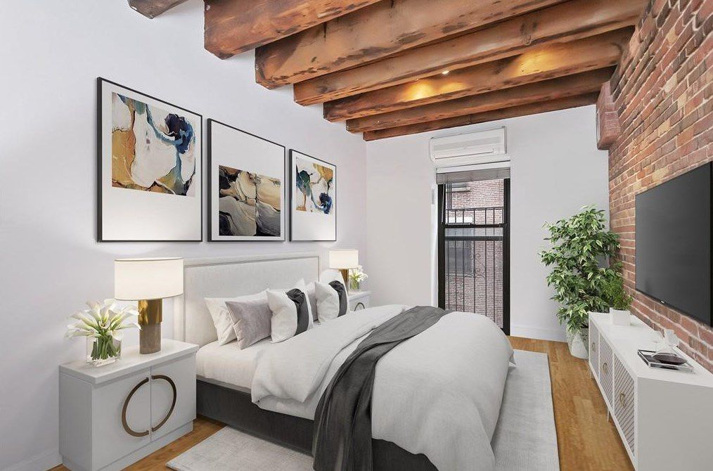 A bedroom with a bed facing a TV, and there's a wood-beam ceiling here too.