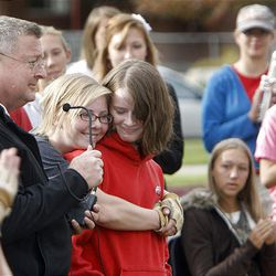 Jordyn Rowland, center left, gives Alexandra Gillies a hug from behind after Gillies addressed her fellow band members after their practice for a competition and the funeral of American Fork High band instructor Heather Christensen, who was killed in a bus accident on their way back from a band competition in Idaho over the weekend. Gillies was the last injured band member released from the hospital; she arrived back at the school as the band started practice. Band director John Miller speaks into a microphone at left.