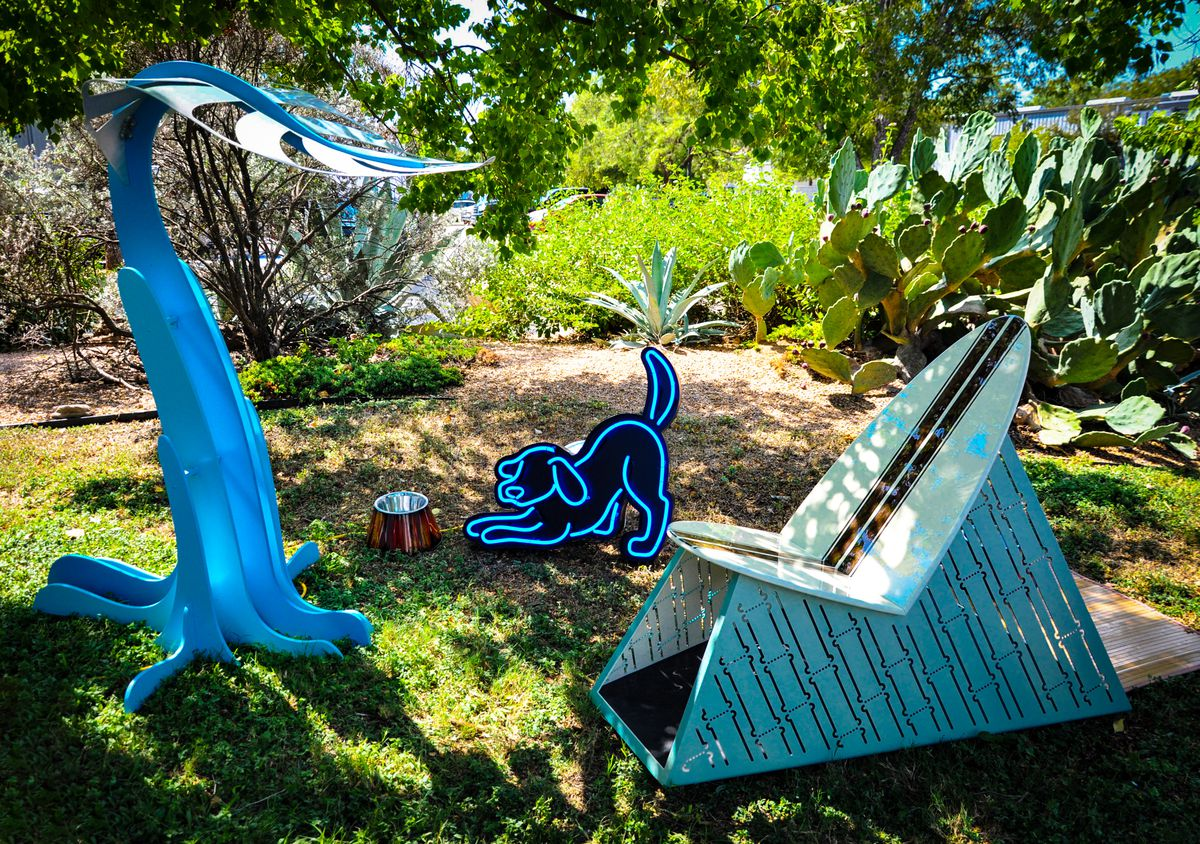 An angular doghouse with a surfboard-like roof, a neon statue of a dog, and a shade sculpture that looks like a giant leaf in a yard.