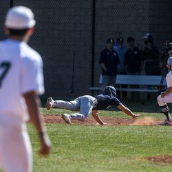 Skyline's Justin Perry (7) dives for first base while Olympus' Jacob Faust (27) tries to get him out during a baseball game at Olympus High School in Holladay on Thursday, April 22, 2021.