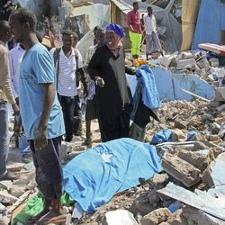 Somalis stand near the body of a civilian who was killed in a car bomb attack in Mogadishu, Somalia Tuesday, June 20, 2017. A number of people are dead after a suicide car bomber in a vehicle posing as a milk delivery van detonated at a district headquarters in Somalia's capital, police said Tuesday.
