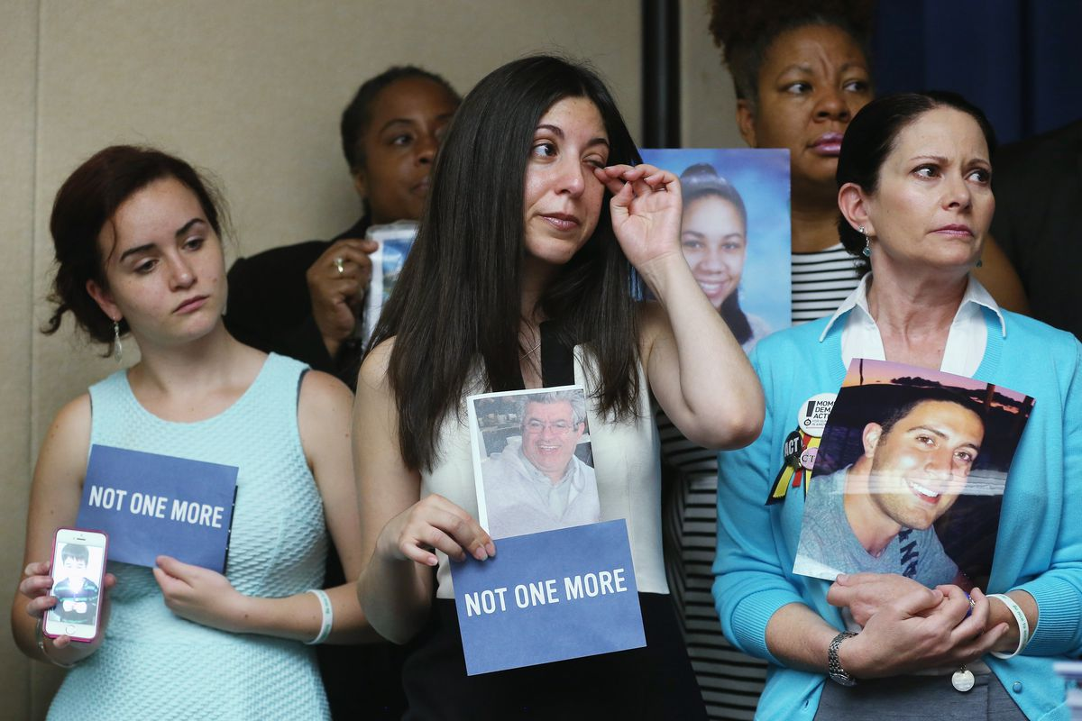 Danielle Vabner (L), Miya Rahamin (C) and Caren Teves (R) hold pictures of loved ones who were killed by gun violence during a news conference on gun safety, on June 17, 2014, in Washington, DC.