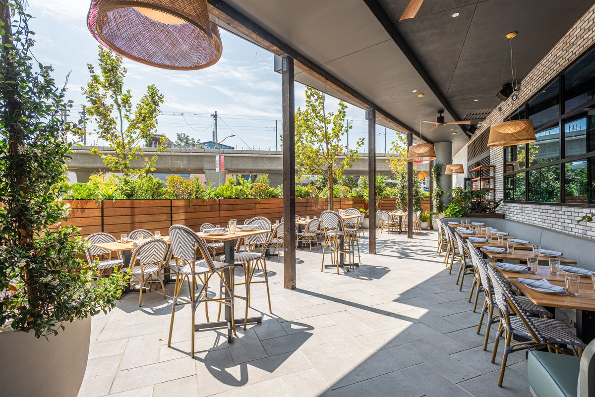 The sunny side of a patio at a new restaurant with woven cafe seats.