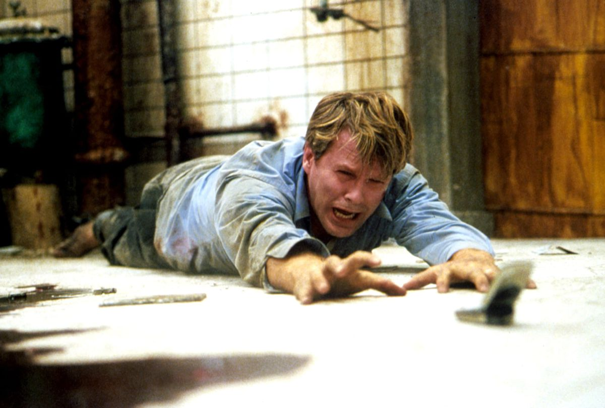 Cary Elwes weeps as he tries to reach a cell phone in the original 2004 Saw