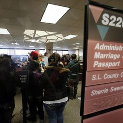 Couples wait to get marriage licenses inside the Salt Lake County clerk's office, Monday, Dec. 23, 2013. U.S. District Judge Robert Shelby denied a motion by the state of Utah to halt same-sex marriages pending an appeal.